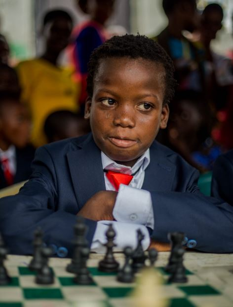 10 year old Ferdinand Maumo sitting ALONE behind the black pieces
