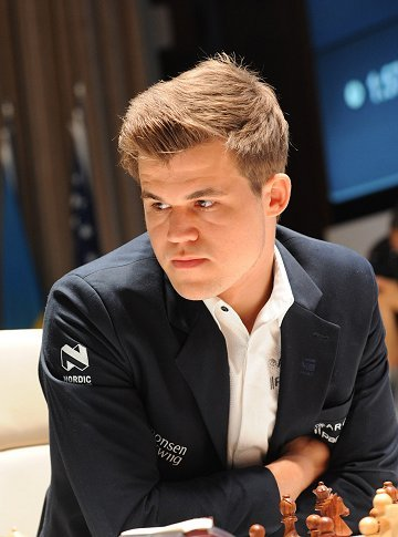 Magnus Carlsen with open collar seated at chess board looking away