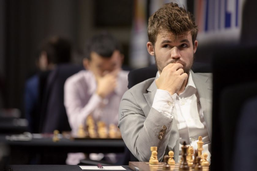 Magnus Carlsen hand to face Ding Liren behind him over left shoulder