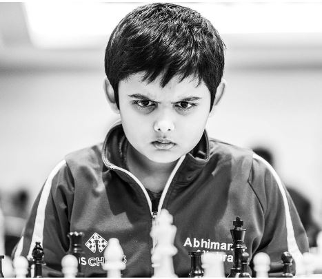 Abhimanyu Mishra black & white glaring at chess board behind black pieces