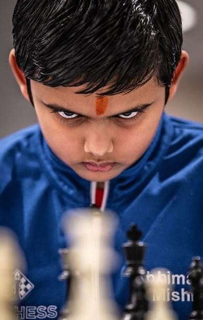 Abhimanyu Mishra color photo really glaring at chess board behind black pieces