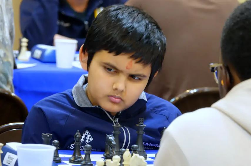 Abhimanyu Mishra in blue jacket sitting at chess board behind black pieces