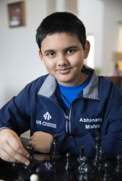 Abhimanyu Mishra smiling sitting behind black chess pieces