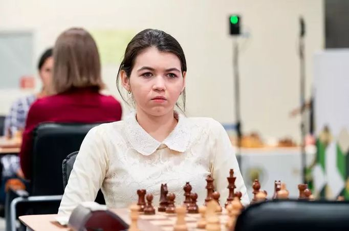 Aleksandra Goryachkina in white sitting at chess board behind black pieces.