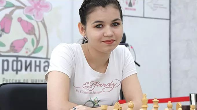 Aleksandra Goryachkina in white short sleeves smile sitting at chess board behind white pieces