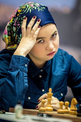 Aleksandra Goryachkina in color blue bandana and coat hand to face at chess board.