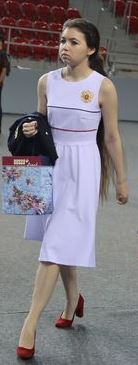 Aleksandra Goryachkina walking in white dress and red shoes