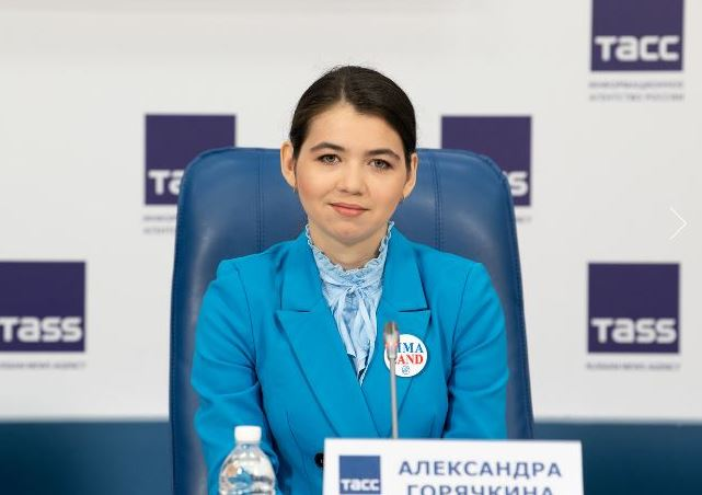Aleksandra Goryachkina in blue top sitting in blue chair looking at camera