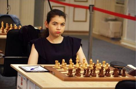 Aleksandra Goryachkina in short-sleaved black top sitting at chessboard behind white pieces