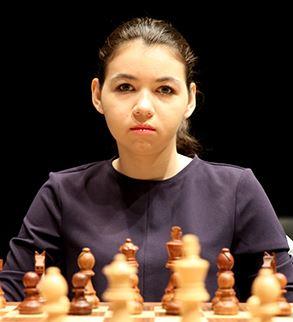 Aleksandra Goryachkina staring at camera in black top sitting behind the black pieces