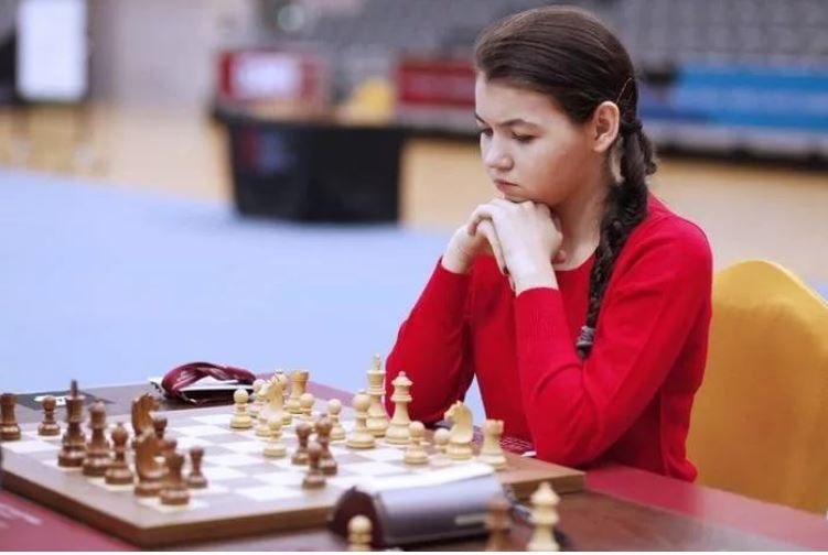 Aleksandra Goryachkina with braided pony tail in red sweater sitting at chessboard behind whites pieces