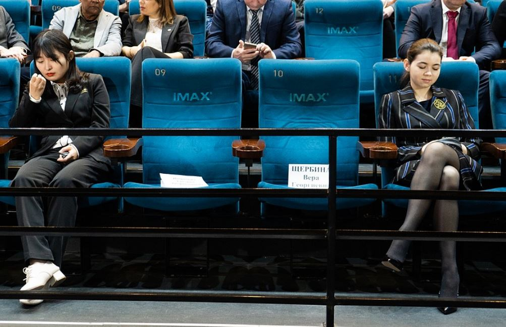 Aleksandra and Ju sitting in blue IMAX chairs two seats apart