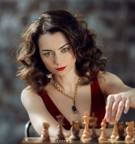 Alexandra Kosteniuk with makeup sitting reaching for white chess piece