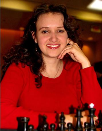 Anna Zatonskih smiling hand to cheek red top black chess pieces.