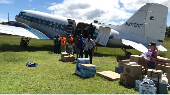 Cargo plane landing on grass field in Pignon with supplies for orphanage and school