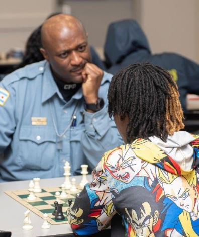 Chicago Chess Cops & Kids black police officer playing chess with kid with dreadlocks