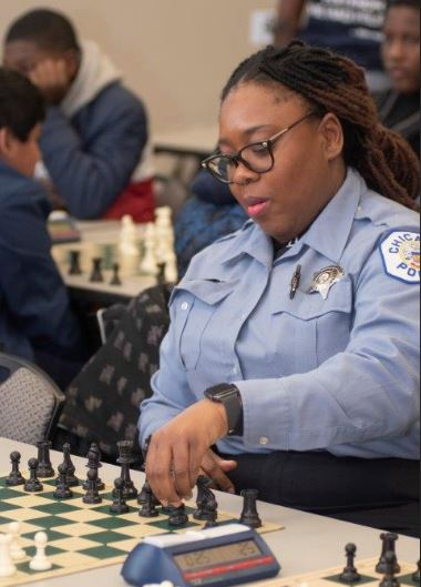 Chicago Chess Cops & Kids female black police officer moving chess pieces