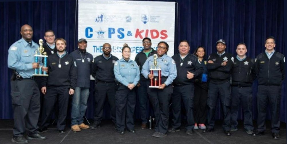 Chicago Chess Cops & Kids group photo of police officers with banner in background