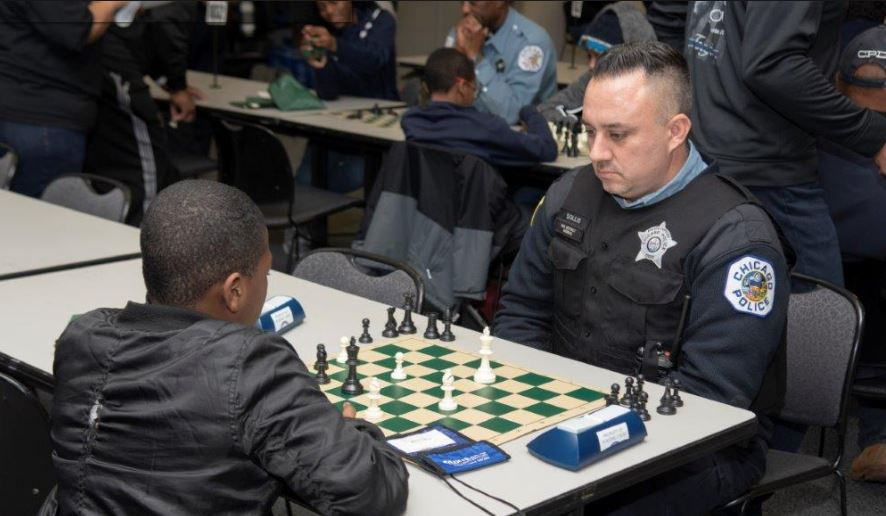 Chicago Chess Cops & Kids white police officer patch on arm playing chess