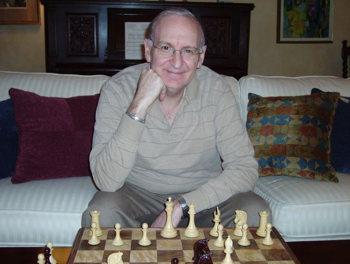 Dan Heisman sitting at chessboard behind white pieces hand to chin smiling