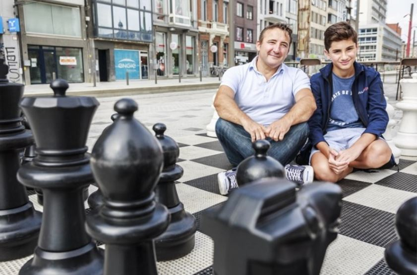 Daniel Dardha with father Arben Dardha sitting on ground in front of large chess set.