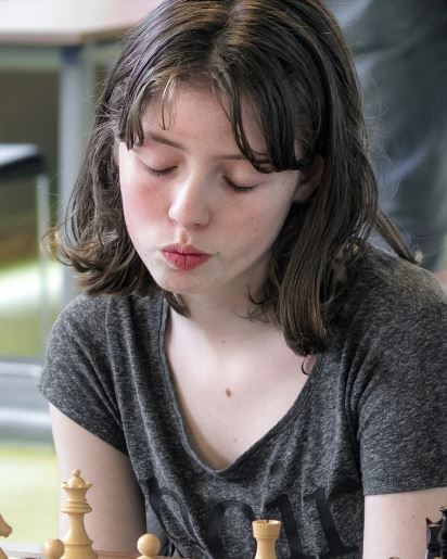 Eline Roebers sitting in gray top lips pursed eyes closed behind the white pieces at the chessboard.
