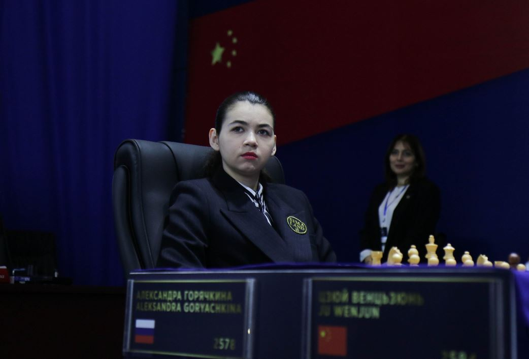 Game 12 Aleksandra Goryachkina in blazer sitting at chessboard at 2020 Women's World Chess Championship