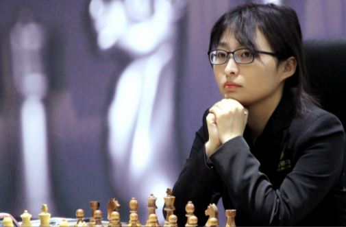 Reigning Champion Ju Wenjun under pressure pawn behind at chessboard in chair