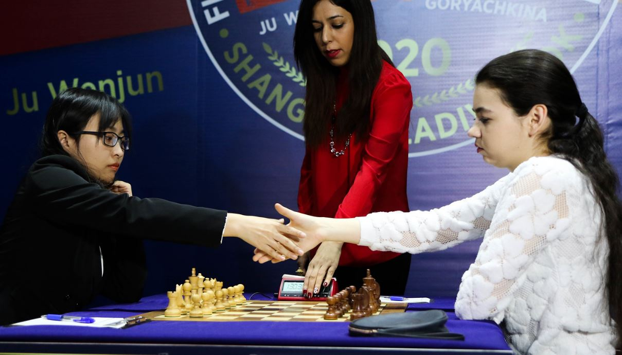 Game 7 Aleksandra and Ju shake hands at chessboard at start of game