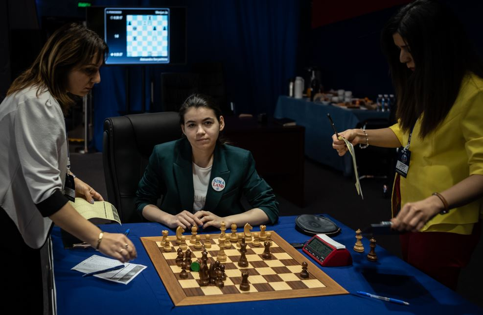 Game 8 challenger Aleksandra sitting at chessboard smiles after winning
