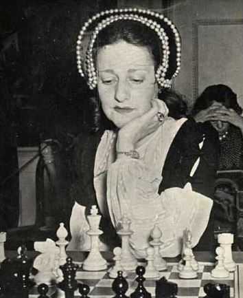Gisela Kahn Gresser black and white portrait wearing striped beaded head covering sitting at chess board behind white pieces