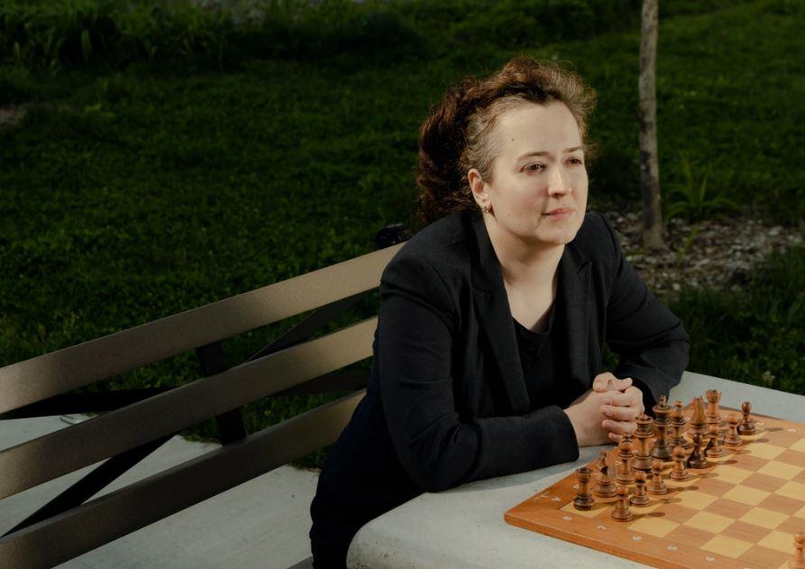 Irina Krush at chessboard in park