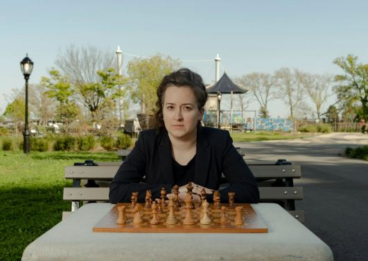 Irina Krush staring at camera at chessboard in park