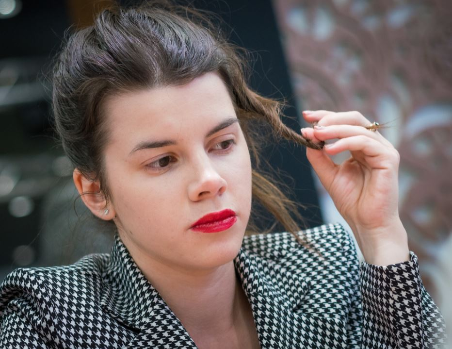 Iulija Osmak red lipstick hand in strand of hair wearing checkered sportscoat
