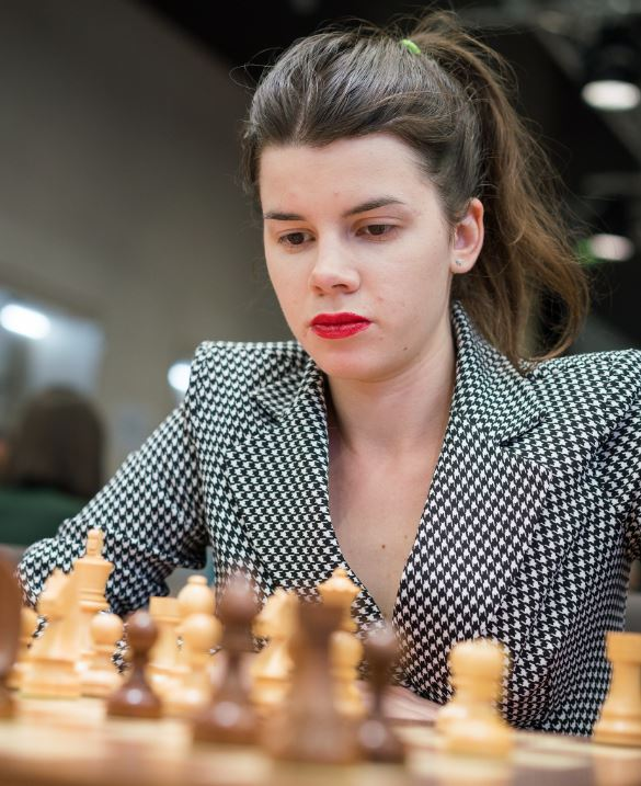 Iulija Osmak seated at chessboard behind black pieces hair in pony tail