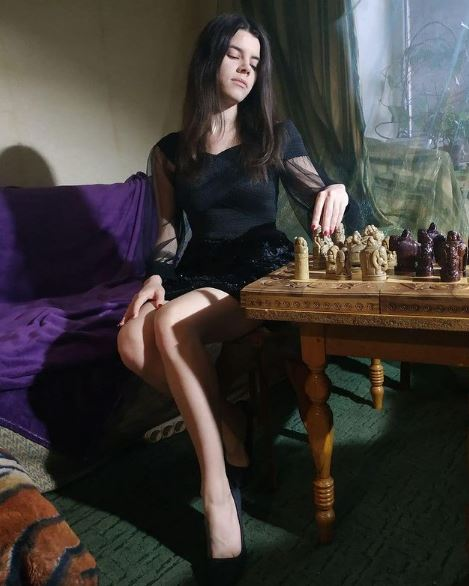 Iulija Osmak seated at chessboard in short dress and high heels