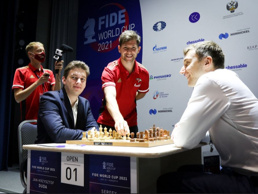 Jan Krzysztof Duda in blue sports coat at the board at the start of a game against Sergy karjakin at 2021 FIDE World Cup