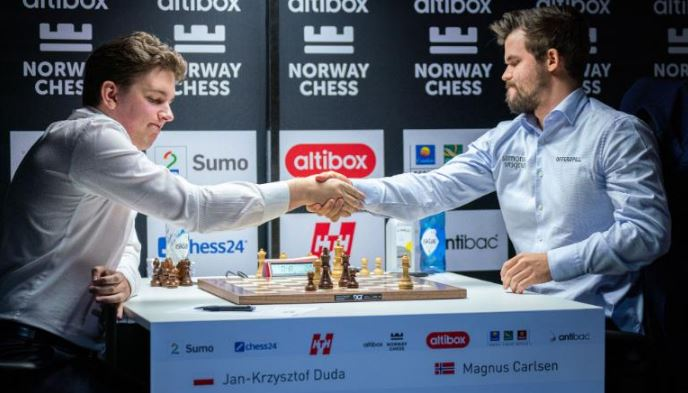 Jan Krzysztof Duda shakes hands with Magnus Carlsen after defeating him