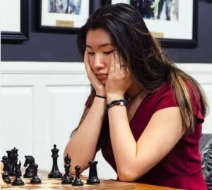Jennifer Yu champion sitting at chessboard hands on cheeks red top playing black pieces.