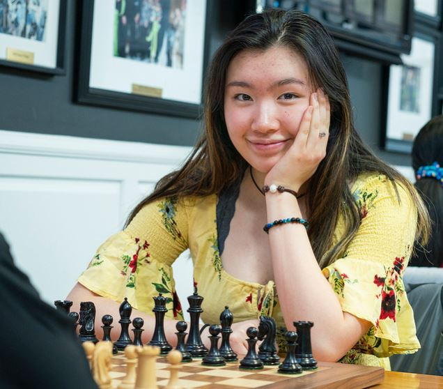 ennifer Yu sitting at chessboard smiling 17 years old