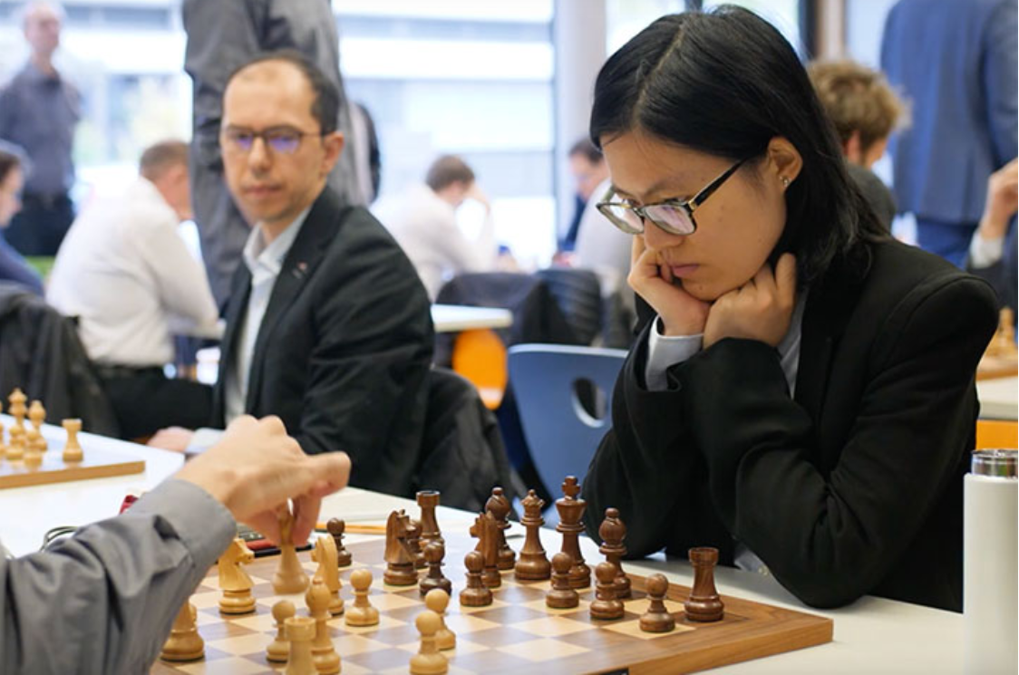 Hou Yifan returns seated behind black pieces 2019 Dec