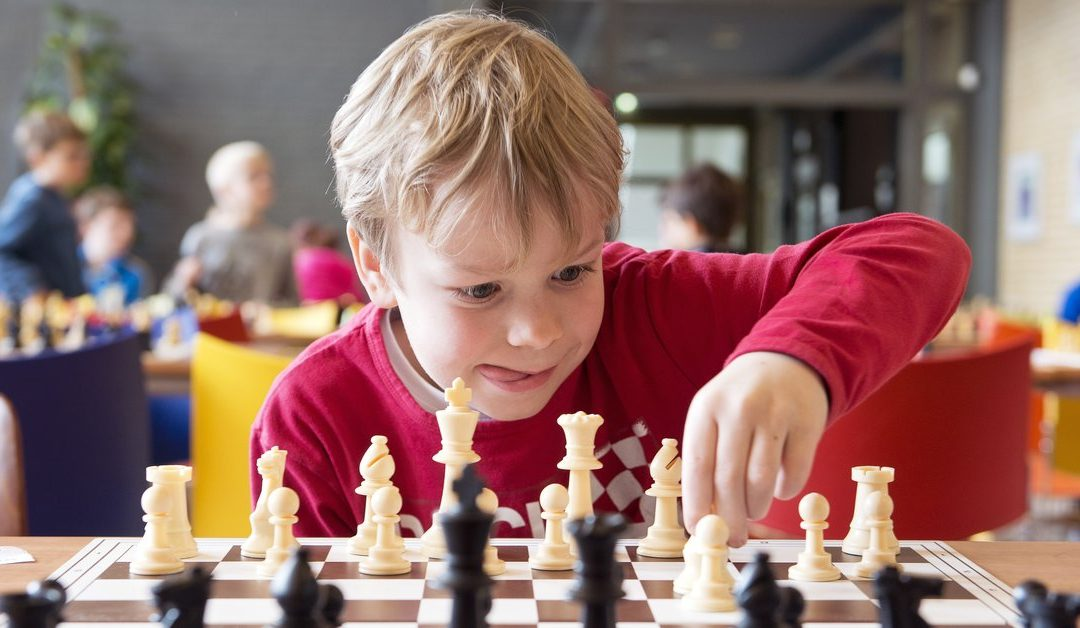 A little boy making a move at a chessboard.