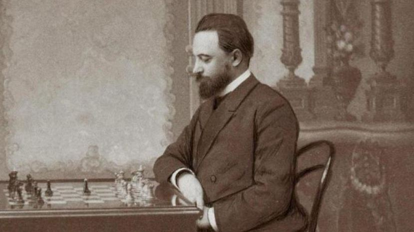 Mikhail Chigorin in old photo sitting at chessboard behind the white pieces