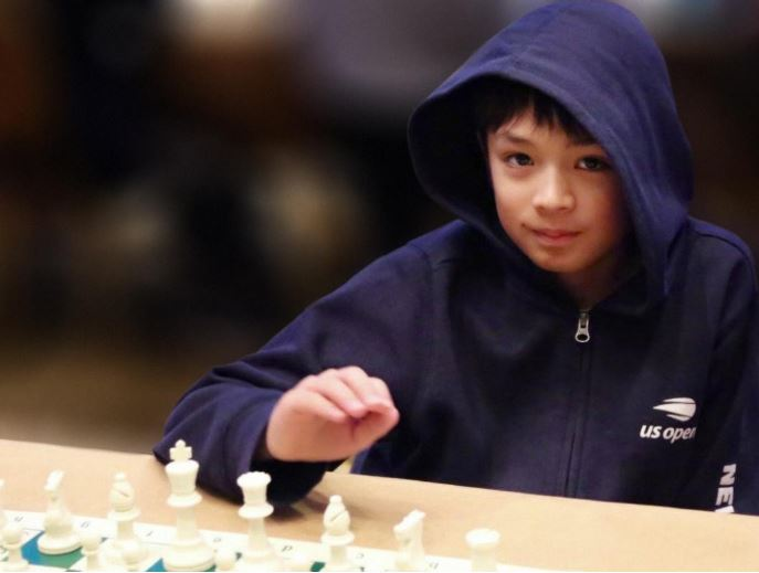 Oliver Boydell cute in hoodie sitting behind white chess pieces