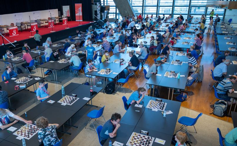 Open Section of tournament players with hands to mouths playing chess no plexiglass shields