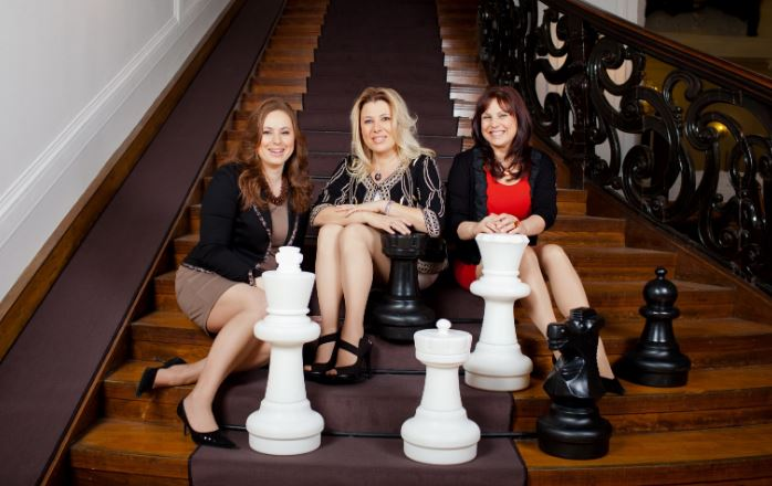Polgar sisters in dresses sitting grand steps.