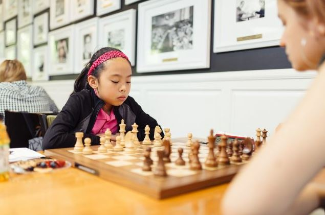 Rachael Li seated at chessboard playing white pieces.