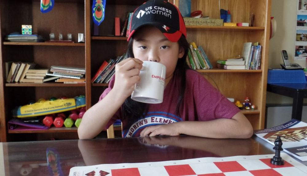 Rachael Li in USA Chess Women cap with coffee cup to mouth.