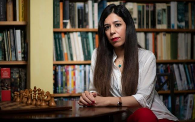 Shohreh Bayat at chess table behind white pieces