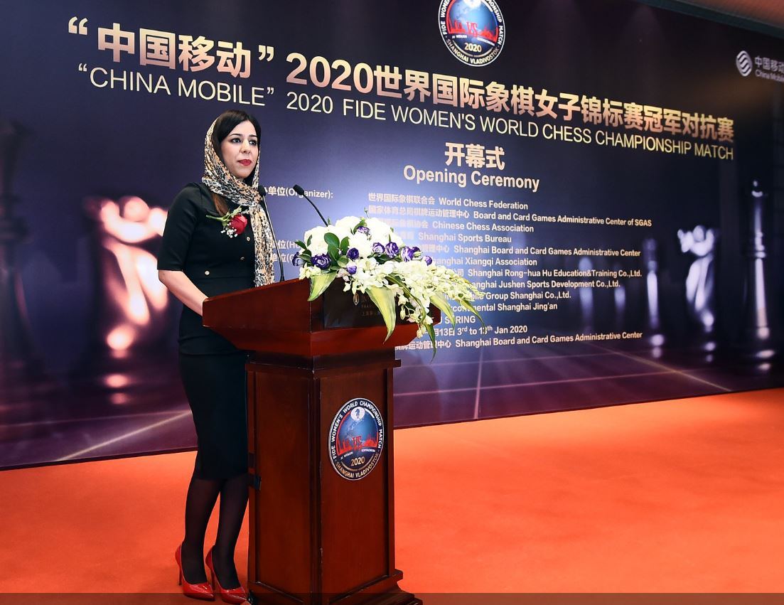 Shohreh Bayat standing at podium in red shoes and wiearing hijab